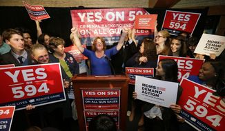 Cheryl Stumbo, center, raises her arms as she finishes speaking at an election night party for Initiative 594, a measure seeking universal background checks on gun sales and transfers, Tuesday, Nov. 4, 2014, in Seattle. Stumbo, the citizen sponsor of the initiative, is a survivor in the shooting at the Jewish Federation in Seattle in 2006. The initiative is one of two competing gun initiatives in Washington state. The other measure, Initiative 591, would prevent any such expansion of background checks. (AP Photo/Elaine Thompson)