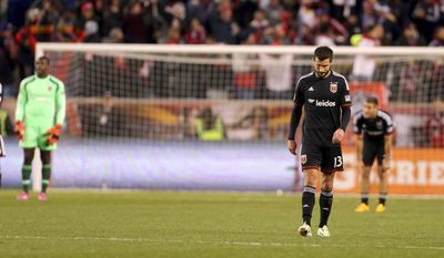 D.C. United Chris Pontius (13) hangs his head after goalkeeper Bill Hamid (28) gave up a goal against the New York Red Bulls during the second half of an MLS playoff soccer match, Sunday, Nov. 2, 2014, in Harrison, N.J. (AP Photo/Adam Hunger)