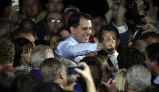 Wisconsin Republican Gov. Scott Walker shakes hands after speaking at his campaign party Tuesday, Nov. 4, 2014, in West Allis, Wis. Walker defeated Democratic gubernatorial challenger Mary Burke. (AP Photo/Morry Gash)