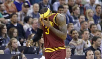Cleveland Cavaliers' LeBron James wipes his face as he walks up court in the second half during an NBA basketball game against the Utah Jazz on Wednesday, Nov. 5, 2014, in Salt Lake City. The Jazz won 102-100. (AP Photo/Rick Bowmer)