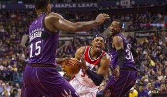 Washington Wizards' Paul Pierce, center, drives between Toronto Raptors' Amir Johnson, left, and Terrence Ross during the first half of an NBA basketball game Friday, Nov. 7, 2014, in Toronto. (AP Photo/The Canadian Press, Chris Young)