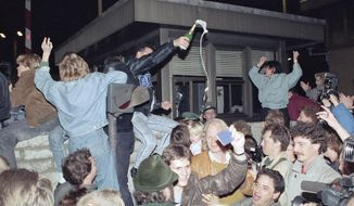 ADVANCE FOR RELEASE SATURDAY, NOVEMBER 8, 2014, AT 12:01 A.M;  NOV. 10, 1989, FILE PHOTO - In this Nov. 10, 1989, file photo, East and West Berliners mingle as they celebrate in front of a control station on East Berlin territory, during the opening of the borders to the West following the announcement by the East German government that the border to the West would be open. (AP Photo/Jockel Finck, File)