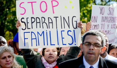 "Sara Ramirez of Gaithersburg, Md., left, holds a sign that reads, ""Stop Separating Families"" as Director of Casa de Maryland Gustavo Torres, right, speaks during an Immigrant rally outside the White House to call on the President to use executive action to help undocumented immigrants since Congress has failed to pass a comprehensive overhaul of immigration laws, Washington, D.C., Friday, November 7, 2014. (Andrew Harnik/The Washington Times)"