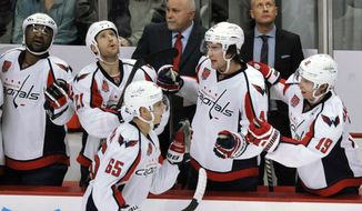 Washington Capitals' Andre Burakovsky (65) celebrates with teammates Tom Wilson, second from right, and Nicklas Backstrom, right, of Sweden, on the bench during the second period of an NHL hockey game against the Chicago Blackhawks in Chicago, Friday, Nov. 7, 2014. Washington won 3-2. (AP Photo/Paul Beaty)