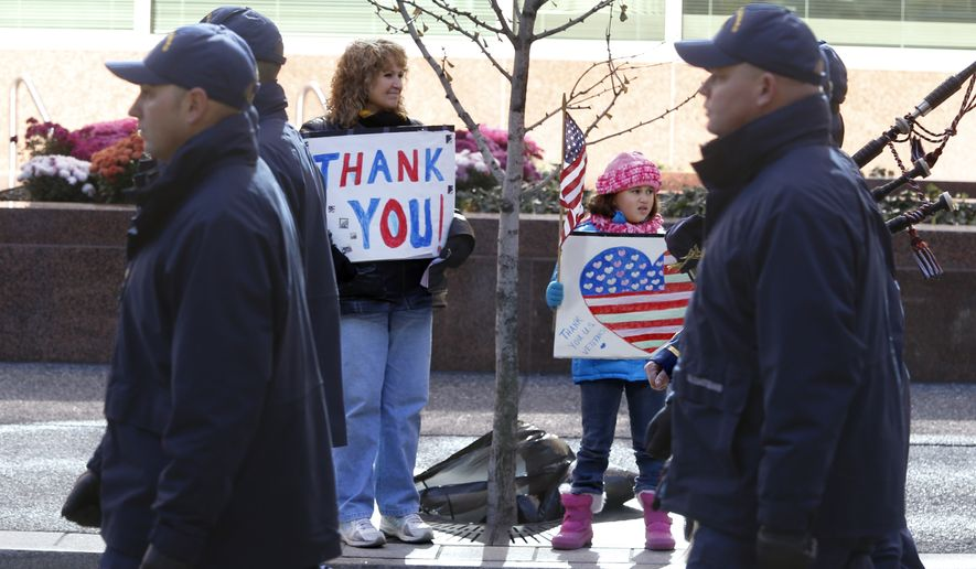 Sue Lippert, center left, and her 7-year-old granddaughter Ava Lippert, center right, hold signs thanking veterans as members of the U.S. Coast Guard march by in the Pittsburgh Veterans Day parade on Saturday, Nov. 8, 2014, in Pittsburgh. Lippert said Ava's mother is currently serving in the Air Force. The city moved their parade to Saturday ahead of the Nov. 11 holiday honoring veterans so more people could attend. (AP Photo/Keith Srakocic)