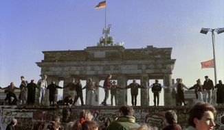 FILE - In this Nov. 10, 1989 file photo Berliners sing and dance on top of The Berlin Wall to celebrate the opening of East-West German borders. Thousands of East German citizens moved into the West after East German authorities opened all border crossing points to the West. In the background is the Brandenburg Gate. (AP Photo/Thomas Kienzle)