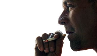 John Cormier smokes a cigarette on Main Street in Westminster, Mass., Thursday, Nov. 6, 2014. Local officials are contemplating what could be a first: a blanket ban on all forms of tobacco and e-cigarettes, leaving some shop owners fuming. (AP Photo/Elise Amendola) ** FILE **