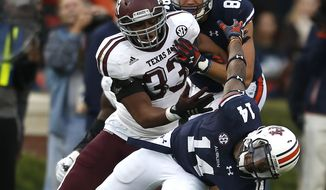 Auburn quarterback Nick Marshall (14) is tackled for a loss by Texas A&M linebacker Shaan Washington (33) during the first half of an NCAA college football game on Saturday, Nov. 8, 2014, in Auburn, Ala. (AP Photo/Butch Dill)