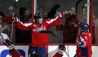 Washington Capitals center Nicklas Backstrom, top left, from Sweden, celebrates with teammates Mike Green (52) and left wing Alex Ovechkin (8), from Russia, after scoring the winning goal with only seconds left in the overtime period of an NHL hockey game against the Carolina Hurricanes, Saturday, Nov. 8, 2014, in Washington. The Capitals won 4-3. (AP Photo/Alex Brandon)
