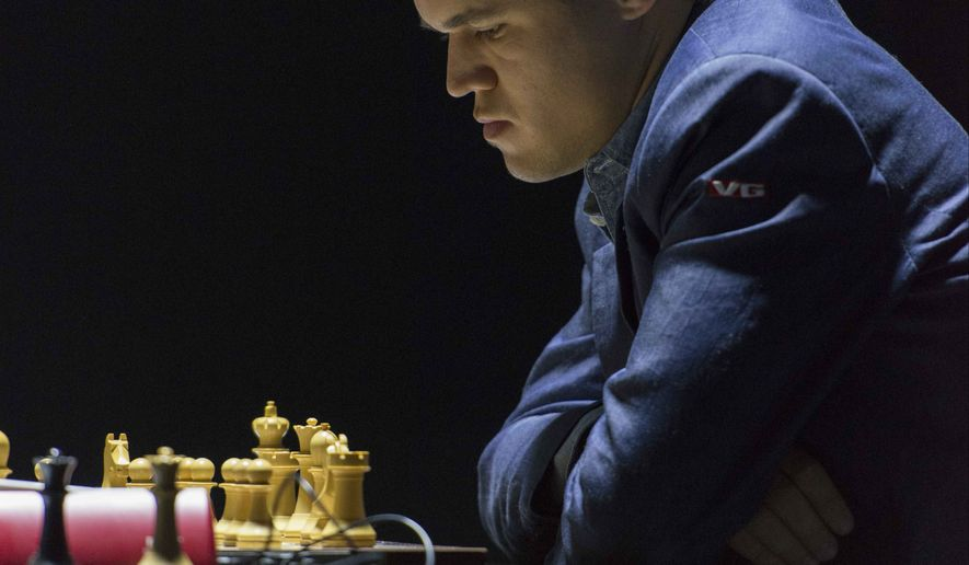 Norway's Magnus Carlsen, currently the top ranked chess player in the world, plays against India's former World Champion Vishwanathan Anand at the FIDE World Chess Championship Match in Sochi, Russia, Sunday, Nov. 9, 2014. (AP Photo/Artur Lebedev)