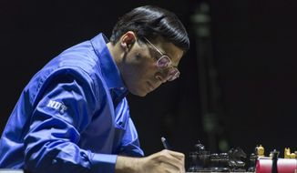 India's former World Champion Vishwanathan Anand makes notes as he plays against Norway's Magnus Carlsen, currently the top ranked chess player in the world, at the FIDE World Chess Championship Match in Sochi, Russia, Sunday, Nov. 9, 2014. (AP Photo/Artur Lebedev)