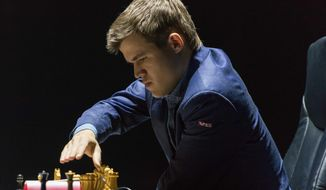 Norway's Magnus Carlsen, currently the top ranked chess player in the world makes a move as he plays against India's former World Champion Vishwanathan Anand at the FIDE World Chess Championship Match in Sochi, Russia, Sunday, Nov. 9, 2014. (AP Photo/Artur Lebedev)