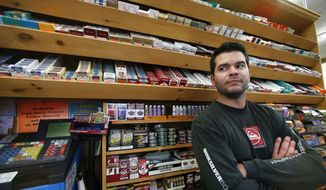 Brian Vincent poses in front of a large display of tobacco products at Vincent's Country Store in Westminster, Mass., Thursday, Nov. 6, 2014. Local officials are contemplating what could be a first: a blanket ban on all forms of tobacco and e-cigarettes, leaving some shop owners fuming. (AP Photo/Elise Amendola)