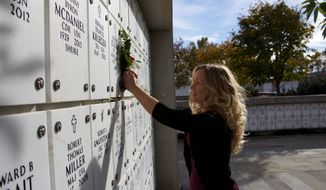 Remembrance: Jaray Simms places flowers at the gravestone of her father, a World War II veteran. The Wreaths Across America volunteer said the annual ceremony next month at Arlington National Cemetery will bring her work full circle. (Catrina Head)