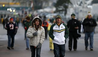 Fans are seen bundled up as they arrive at Lambeau Field before of an NFL football game between the Green Bay Packers and the Chicago Bears Sunday, Nov. 9, 2014, in Green Bay, Wis. (AP Photo/Kiichiro Sato)
