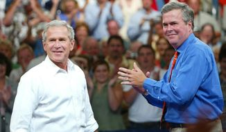 In this Aug. 10, 2004 file photo, President George W. Bush, left, is introduced by his brother Florida Gov. Jeb Bush, right, at  'Ask President Bush' campaign rally, at Okaloosa-Walton Community College Gymnasium in Niceville, Fla. (Associated Press) **FILE**
