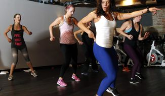 "In this Oct. 30, 2014 photo, Kelly Brabants, foreground, leads her ""Booty by Brabants"" class at The Club by George Foreman III gym in Boston. The class, started by Brabants a year ago, fits in 120 squats in 45 minutes. (AP Photo/Elise Amendola)"