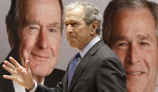 """Former President George W. Bush passes by a portrait of himself and his father former President George H.W. Bush as he takes the stage to discuss his new book, """"41: A Portrait of My Father"""" at the his father's presidential library Tuesday, Nov. 11, 2014, in College Station, Texas. (AP Photo/Pat Sullivan)"""