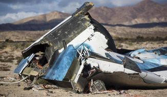 FILE - In this Saturday, Nov. 1, 2014, file photo, wreckage lies near the site where a Virgin Galactic space tourism rocket, SpaceShipTwo, exploded and crashed in Mojave, Calif. The surviving pilot of the Virgin Galactic spaceship that tore apart over the Mojave Desert was thrown clear of the disintegrating craft and did not know his co-pilot had prematurely unlocked the re-entry braking system, federal investigators said Wednesday, Nov. 12, 2014. (AP Photo/Ringo H.W. Chiu, File)