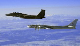 """This Thursday, Sept. 28, 2006, file photo provided by the U.S. Air Force shows an F-15C Eagle from the 12th Fighter Squadron at Elmendorf Air Force Base in Anchorage, Alaska, flying next to a Russian Tu-95 """"Bear"""" bomber, right, during a Russian exercise which brought the bomber near the west coast of Alaska. (AP Photo/U.S. Air Force) ** FILE **"""