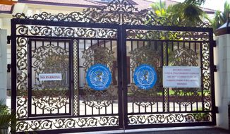 This Saturday, Nov. 8, 2014 photo shows the entrance to the office of World Health Organization in Yangon, Myanmar. The World Health Organization's office, surrounded by an eight-foot high fence and an iron gate, says it is paying around $80,000 a month for its office in this garish mansion in Myanmar's crumbling old capital.  With the lifting of most sanctions and the easing of diplomatic pressure after the former pariah state began its transition to democracy, foreign donors, international aid organizations and multinational companies started flooding into the country. That has pushed rents sky-high, some organizations putting up to a $1 million dollars a year into the pockets of former and current generals and cronies.  (AP Photo/Khin Maung Win)