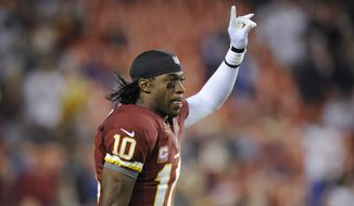 Washington Redskins quarterback Robert Griffin III acknowledges the crowd as he runs on to the field to warm up before an NFL football game against the New York Giants in Landover, Md., Monday, Dec. 3, 2012. (AP Photo/Nick Wass)