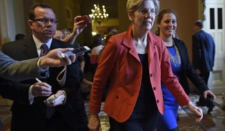 Sen. Elizabeth Warren, D-Mass. is pursued by reporters on Capitol Hill in Washington, Thursday, Nov. 13, 2014. Officials said Sen. Warren, a favorite of liberals, would be given a seat at the Democrats leadership table.  (AP Photo/Susan Walsh)