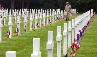 An unidentified visitor wearing a U.S. military nurse uniform walks past graves at the American cemetery, in Colleville-sur-Mer, western France, on June 6, 2007, marking the 63rd anniversary of the D-Day landings in Normandy. (Associated Press) **FILE**