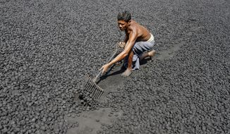An Indian laborer works at a gol coal factory, where coal is made from its fine powdered form, in the eastern Indian city of Bhubaneswar, India, Friday, Nov. 14, 2014. This week's China-U.S. climate agreement between the world's top two polluters puts pressure on India, No. 3 on the list, to become more energy efficient and should encourage investment in renewable energy. (AP Photo/Biswaranjan Rout)