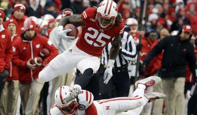 Wisconsin's Melvin Gordon (25) breaks away from Nebraska's Corey Cooper for a 62-yard touchdown run during the first half of an NCAA college football game Saturday, Nov. 15, 2014, in Madison, Wis. (AP Photo/Morry Gash)