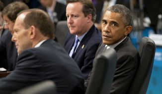 U.S. President Barack Obama, right, looks away as Prime Minister of Australia Tony Abbott, left, address a plenary session while British Prime Minister David Cameron looks on during the G-20 summit in Brisbane, Australia, Saturday, Nov. 15, 2014. (AP Photo/Rob Griffith, Pool) ** FILE **