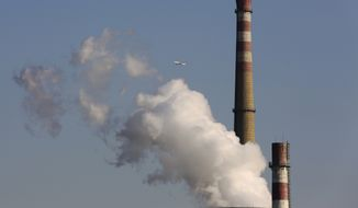 In this Nov. 13, 2014, photo, a passenger airliner flies past smokes emitted from a coal-fired power plant in Beijing, China. A coalition of rights groups wants G-20 leaders to take action to improve the lives of the most vulnerable in society, reduce inequality and address climate change. (AP Photo/Andy Wong, File)