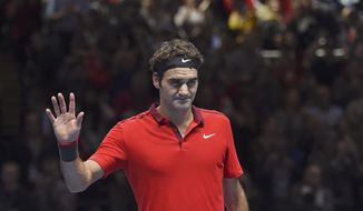 Switzerland's Roger Federer celebrates winning his ATP World Tour Finals semifinal tennis match against his compatriot Stan Wawrinka at the O2 Arena in London, England, Saturday, Nov. 15, 2014. (AP Photo/Tim Ireland)