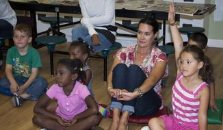 In this June 2014 photo provided by Transition House, a homeless shelter in Santa Barbara, Calif., volunteer Jodi Kirkland, center right, helps out with Transition House's children's program at the shelter. A new report released Monday, Nov. 17, 2014, by the National Center on Family Homelessness says that one fifth of America's homeless children are in California. (AP Photo/Transition House, Kimberly Kavish)