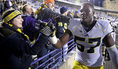 Michigan defensive end Frank Clark (57) celebrates with fans  after Michigan defeated Northwestern 10-9 in an NCAA college football game in Evanston, Ill., Saturday, Nov. 8, 2014. (AP Photo/Nam Y. Huh)