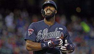 Atlanta Braves' Jason Heyward, who wears an extension to his helmet covering part of his face, grimaces after fouling a ball off of his foot during an at bat against Texas Rangers' Derek Holland in the first inning of a baseball game, Friday, Sept. 12, 2014, in Arlington, Texas. (AP Photo/Tony Gutierrez)