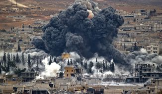 Smoke rises from the Syrian city of Kobani, following an airstrike by the US led coalition, seen from a hilltop outside Suruc, on the Turkey-Syria border Monday, Nov. 17, 2014. Kobani, also known as Ayn Arab, and its surrounding areas, has been under assault by extremists of the Islamic State group since mid-September and is being defended by Kurdish fighters. (AP Photo/Vadim Ghirda)