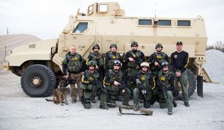 In this undated handout photo provided by the Lancaster County Sheriff's Office, the Lancaster County Sheriff's Office Tactical Response Unit poses in front of a MRAP (Mine-Resistant Ambush Protected) Armored Vehicle, a surplus military vehicle that came through a federal program, in Lincoln, Neb. (AP Photo/Lancaster County Sheriff's Office)