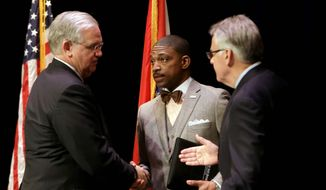 Missouri Gov. Jay Nixon (left) meets with Rev. Starsky Wilson (center) and Rich McClure (right) after swearing the two men in as co-chairs of the 16-member Ferguson Commission in St. Louis Tuesday. The independent commission has been created to study issues that have surfaced since the fatal police shooting of Michael Brown. (Associated Press)