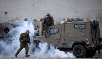 Israeli soldiers run from tear gas, after Palestinians threw canisters fired at them back towards the soldiers, during clashes outside the Ofer military prison, near the West Bank city of Ramallah, Tuesday, Nov. 18, 2014. Two Palestinian cousins armed with meat cleavers and a gun stormed a Jerusalem synagogue during morning prayers Tuesday, killing four people in the city's bloodiest attack in years. The attack ratcheted up fears of sustained violence in a city already on edge amid soaring tensions over its most contested holy site. (AP Photo/Majdi Mohammed)
