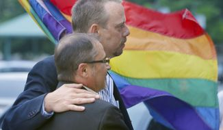 In this photo taken May 12, 2014, Shon DeArmon, top, and his partner James Porter carry a flag in support of the county issuing marriage licenses for same-sex couples at the Pulaski County Courthouse in Little Rock, Ark.  A 2004 amendment to the Arkansas constitution lands before two courts Thursday, Nov. 20, 2014, with the state Supreme Court and a federal judge considering separate challenges in the case. (AP Photo/Danny Johnston)