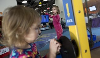 In this Dec. 13, 2012 file photo, children play at the National Children's Museum in Oxon Hill, Md. The National Children's Museum plans to return to the District of Columbia next year, just two years after moving to the National Harbor development in Prince George's County. Museum officials said that they want the institution's new home to be near a Metro station and to have plenty of room to expand. The board decided an expansion at National Harbor would be unaffordable, said Ross Hechinger, chairman of the museum's board of directors. (AP Photo/Jacquelyn Martin, File) *FILE*