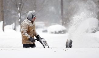 Ken Velie clears snow from his driveway on Wednesday, Nov. 19, 2014, in Lancaster, N.Y. Lake-effect snow pummeled areas around Buffalo for a second straight day, leaving residents stuck in their homes as officials tried to clear massive snow mounds with another storm looming. (AP Photo/Mike Groll)