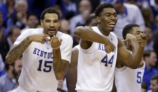 Kentucky's Willie Cauley-Stein (15) and Dakari Johnson (44) celebrate from the bench late in the second half of an NCAA college basketball game against Kansas, Tuesday, Nov. 18, 2014, in Indianapolis. Kentucky won 72-40. (AP Photo/Darron Cummings)