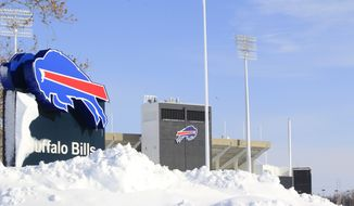 Snow covers a sign at Ralph Wilson Stadium, home of the Buffalo Bills in Orchard Park, N.Y. on Wednesday, Nov. 19, 2014. A ferocious lake-effect storm left the Buffalo area buried under 6 feet of snow Wednesday, trapping people on highways and in homes, and another storm expected to drop 2 to 3 feet more was on its way. (AP Photo/The Buffalo News, Harry Scull Jr.)