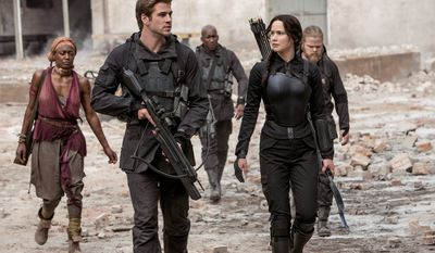 "Jennifer Lawrence stars as Katniss Everdeen with Liam Hemsworth as Gale Hawthorne in ""The Hunger Games: Mockingjay Part 1."" There's a lot that doesn't add up in the latest entry from the first half of the final book in the series of popular young adult novels. (Lionsgate via Associated Press)"