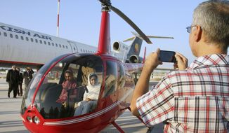 A visitor takes a picture of his company in an R-44 U.S.-made helicopter in an air exhibition in the Iranian Kish Island in the Persian Gulf, Thursday, Nov. 20, 2014. An Iranian company displayed four brand new R-44 U.S.-made helicopters during the air exhibition it says were purchased through third parties, offering them as proof that the country could evade international sanctions over its disputed nuclear program. (AP Photo/Mehr News Agency, Zohreh Saberi)