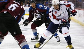 Washington Capitals right wing Alex Ovechkin, center, of Russia, works way with puck between Colorado Avalanche right wing Jarome Iginla, back, and defenseman Erik Johnson in the second period of an NHL hockey game in Denver on Thursday, Nov. 20, 2014. (AP Photo/David Zalubowski)
