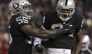 Oakland Raiders cornerback Charles Woodson (24) celebrates with outside linebacker Sio Moore (55) after tackling Kansas City Chiefs running back Jamaal Charles during the first quarter of an NFL football game in Oakland, Calif., Thursday, Nov. 20, 2014. (AP Photo/Jeff Chiu)