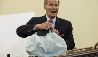 Senate Commerce Committee member Sen. Bill Nelson, D-Fla. displays the parts and function of a defective airbag made by Takata of Japan that has been linked to multiple deaths and injuries in cars driven in the US, Thursday, Nov. 20, 2014, during the committee's hearing on Capitol Hill in Washington.  (AP Photo/J. Scott Applewhite)